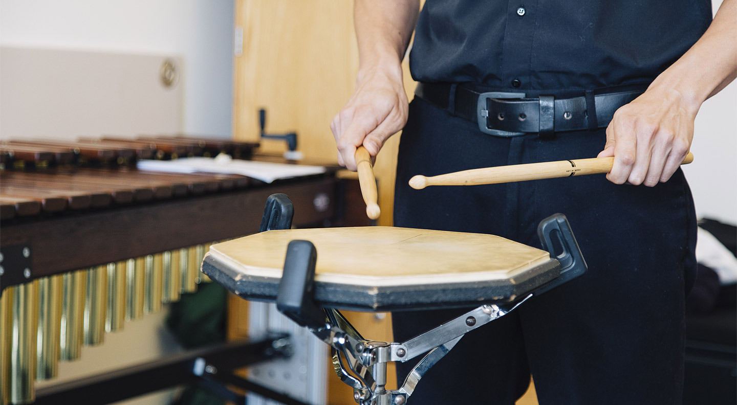 Student plays the drums.