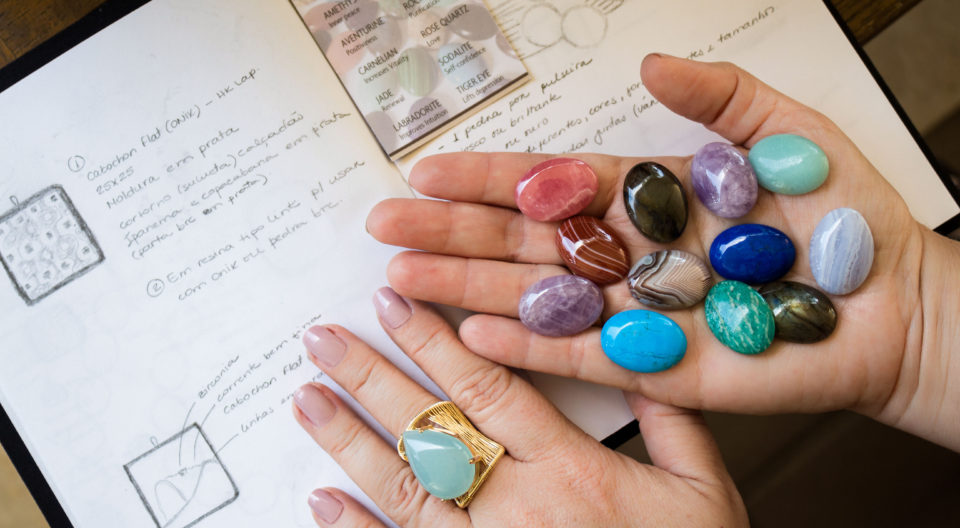 Anny Stern holds gemstones above her sketchbook