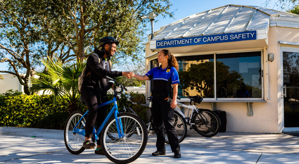 Campus safety officer conversing with student outside of Department of Campus Safety office