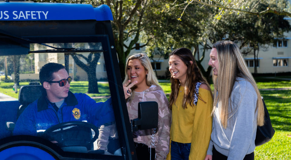 Campus safety officer conversing with three students in official Lynn University Campus Safety golf cart.