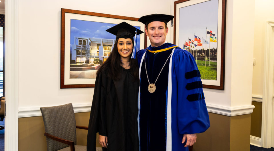 MBA graduate Pakeezah Zubairi poses proudly in graduation attire with President Kevin M. Ross.