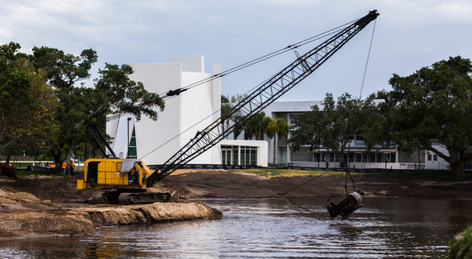 Construction workers use machines to reshape the lake