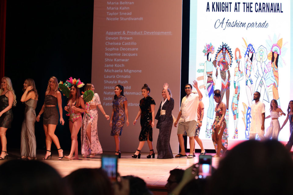 Student volunteers, fashion designers and models walk the stage