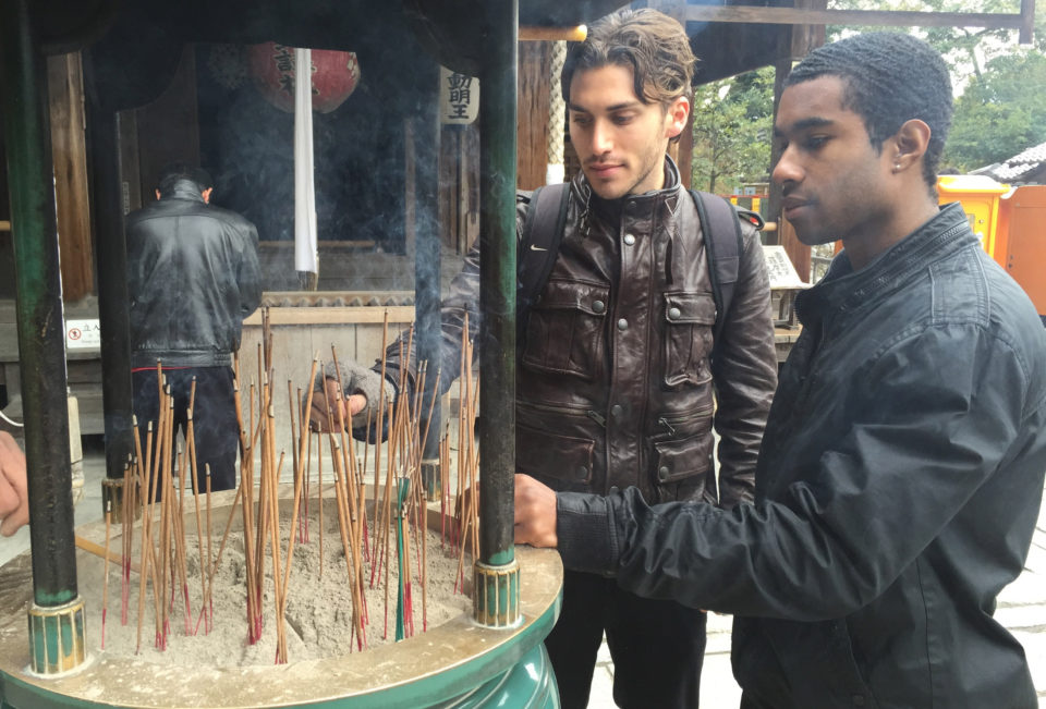 students place incense sticks in sand