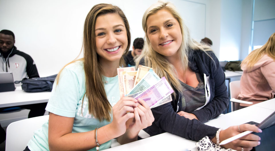 Students hold Indian rupees.