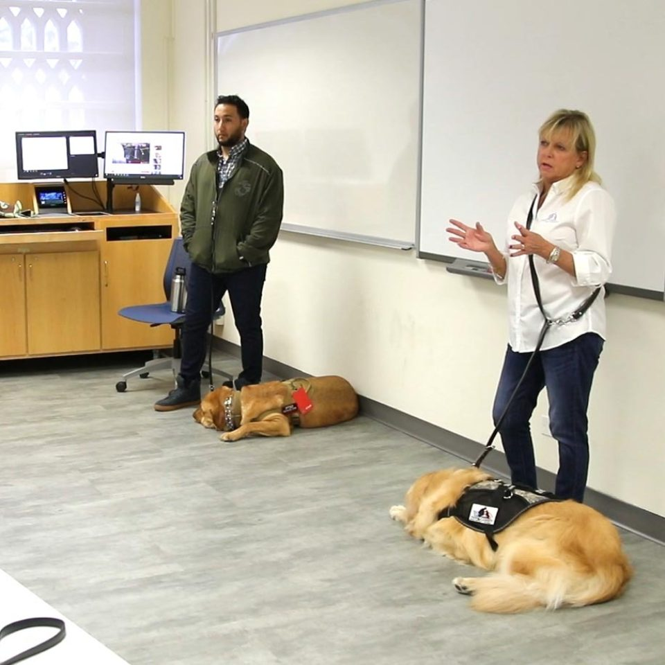 A veteran joins Paws 4 Liberty's co-founder to present about service animals during J-Term 2018.