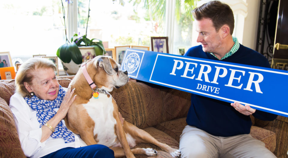 "Kevin M. Ross presents Mrs. Mary Ann Perper and her dog with a new campus street sign, ""Perper Drive."""