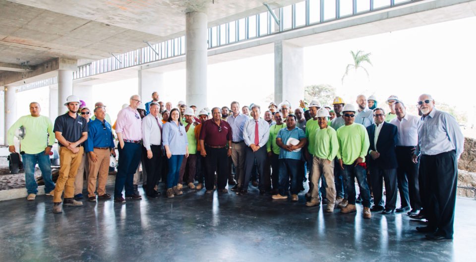 Construction workers, architects, administrators and alumni in Lynn University Center construction site
