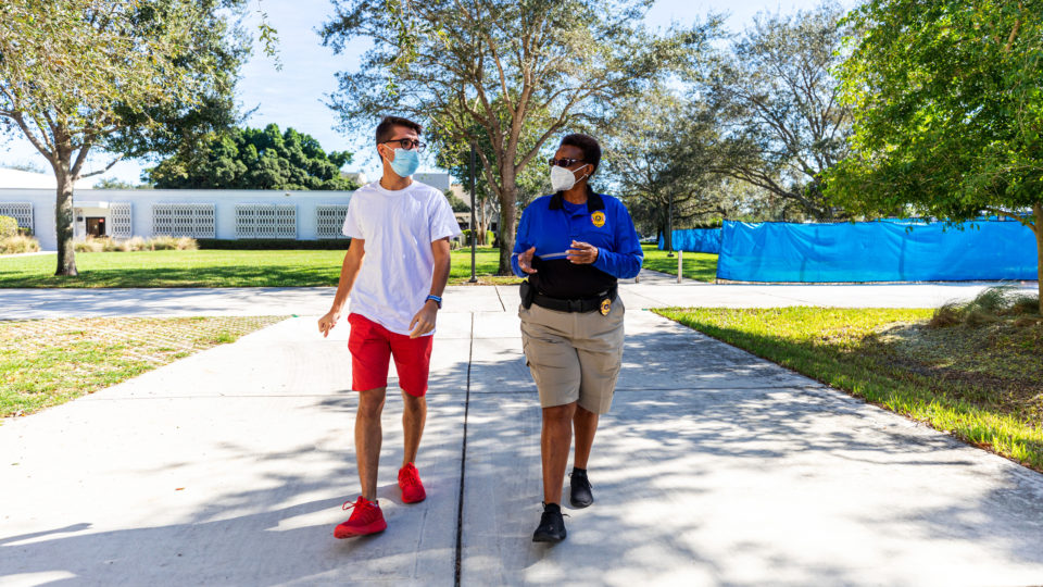 Campus safety officer walks with a student on campus