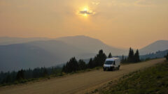 A campervan drives down the road at sunset with a view of mountains in the background.