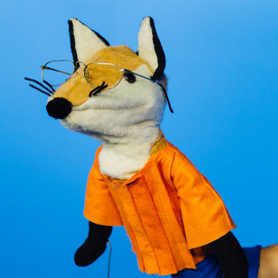Fox puppet wearing an orange shirt and glasses.