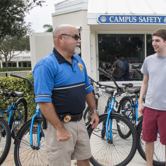 Students speaking with a campus safety security guard.