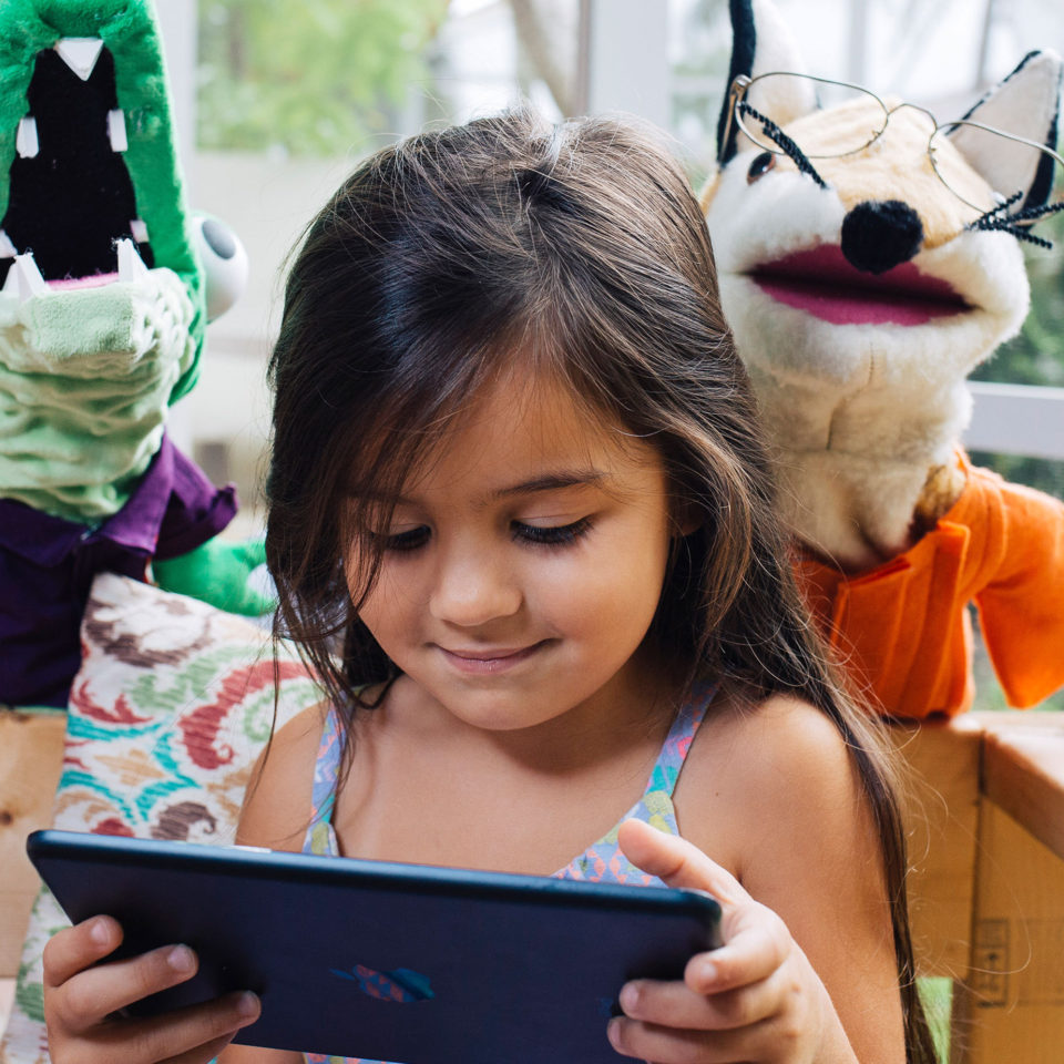 Child using the Language Book app on iPad with two ABC Mouse puppets.
