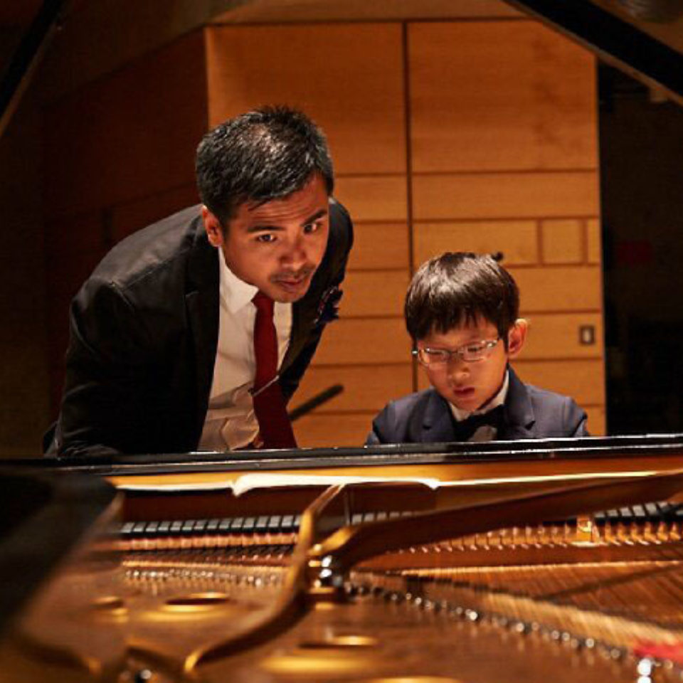 Ross Edillor Salvosa teaches a young student at the piano