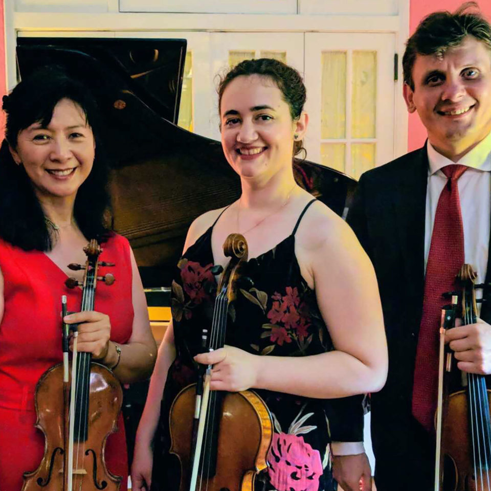 Alumna, Felicia Besan smiles for a photo with the Delray Strings Quartet.