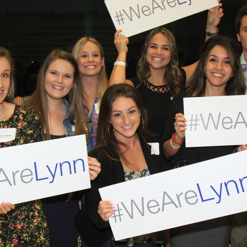 "Alumni hold ""We are Lynn"" signs during alumni week."