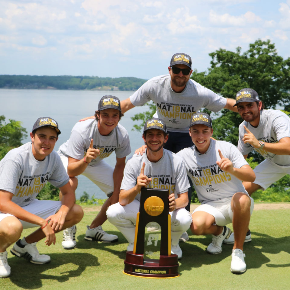 Lynn University Fighting Knights Men's Golf Team pose with Coach Andrew Danna and the 2017-2018 NCAA Division II National Championship trophy
