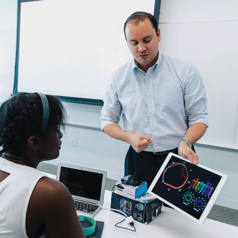 Dr. Matteo Peroni, assistant professor of marketing in the College of Business and Management, uses an iPad and device measuring brain activity to show how consumers react to commercials.