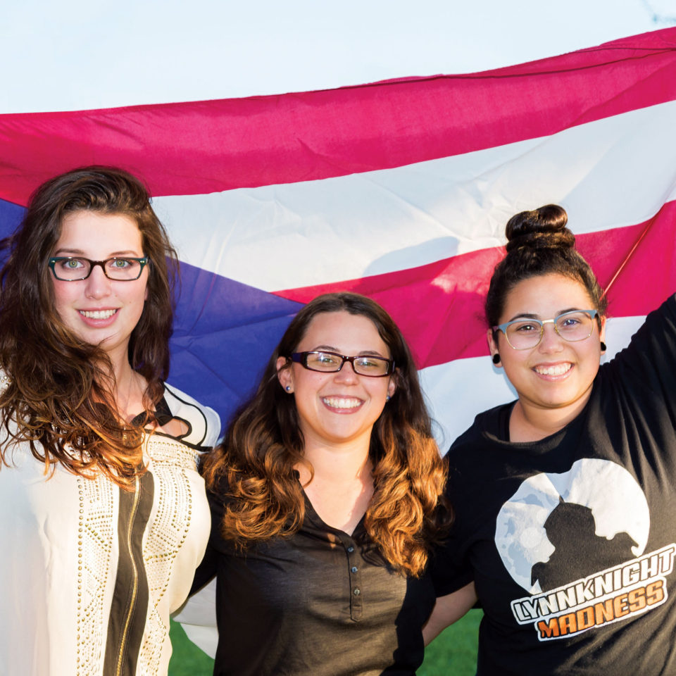 Students raise the Puerto Rican flag.