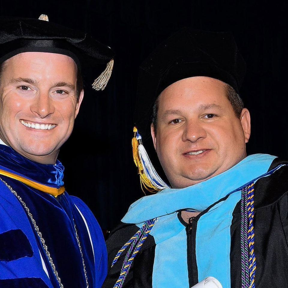 President Kevin M. Ross shakes the hand of graduate Vin Capone at Commencement.