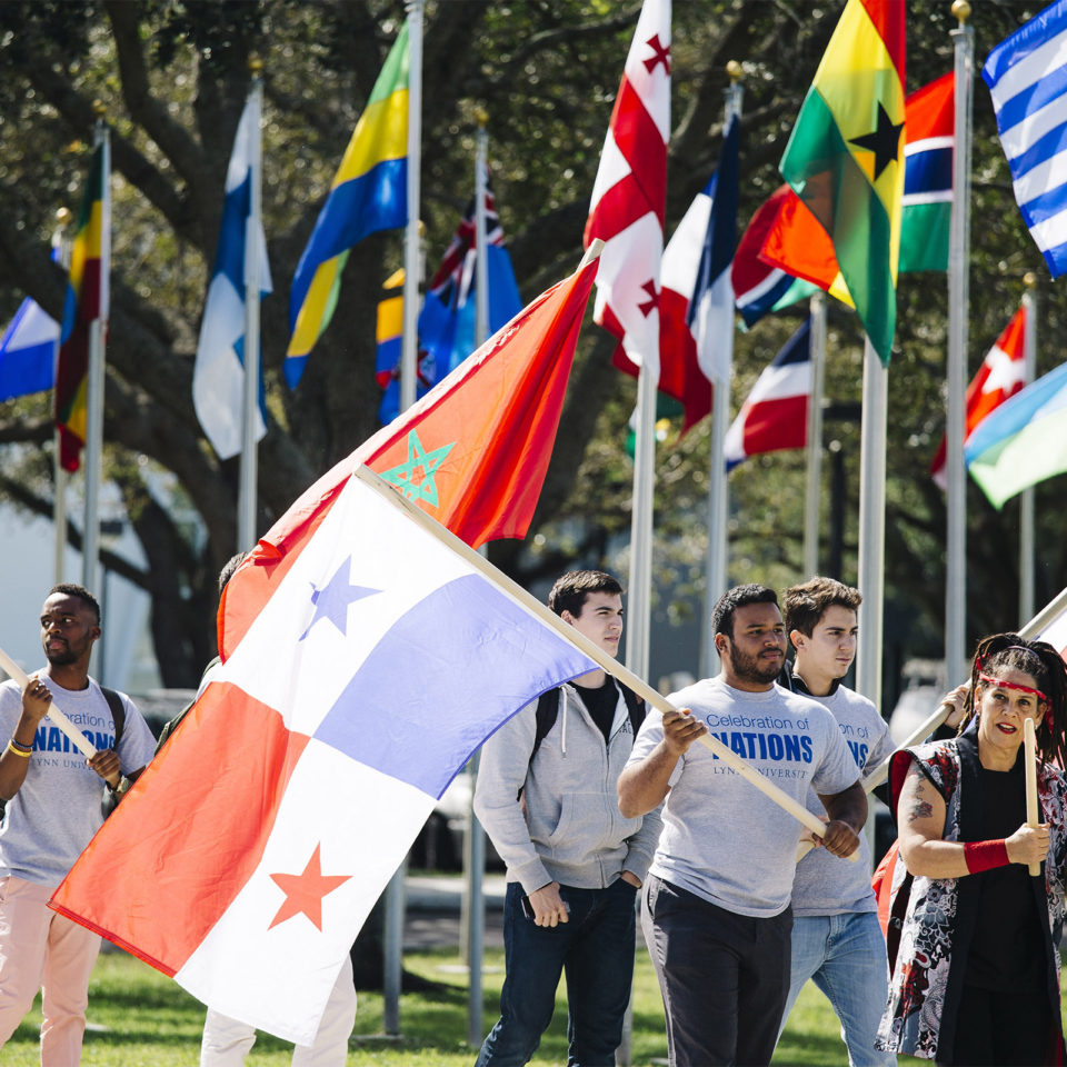 Students holding flags to symbolize the multitude of foreign students welcomed to Lynn University each year.