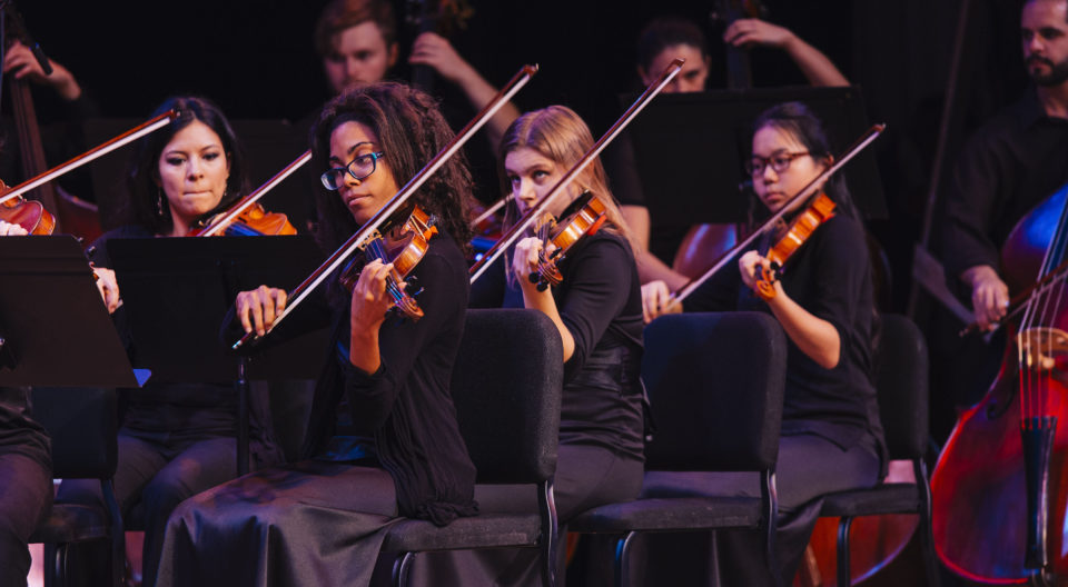 Students play their string instruments in a concert.