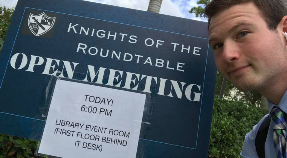 KOR's Chase Cohen poses with open meeting sign