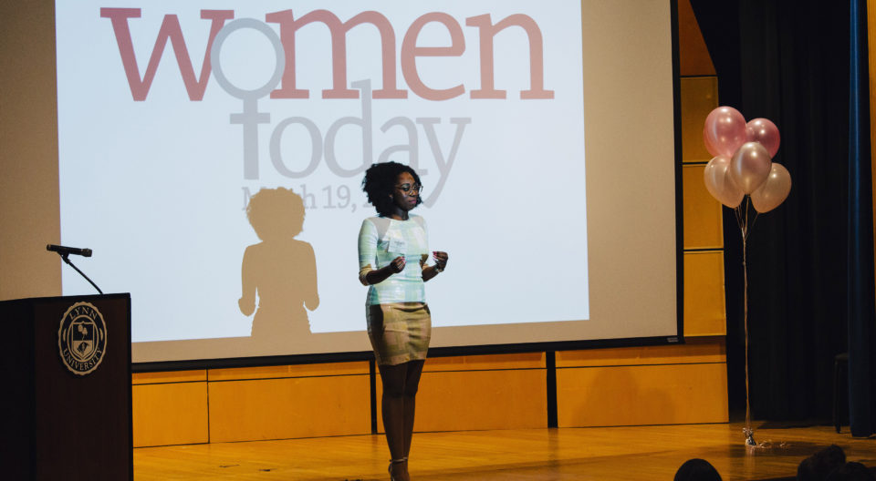 A woman speaks on stage at the luncheon hosted by the Women's Center.