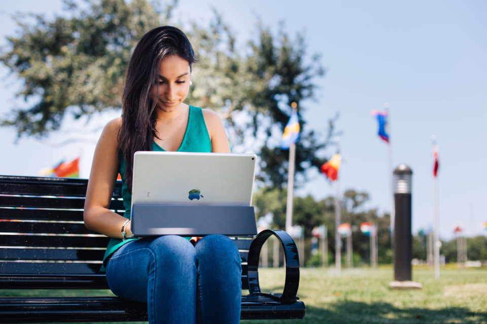 Undergraduate international student, Eloisa Sarmiento, uses her iPad Pro with keyboard outside.