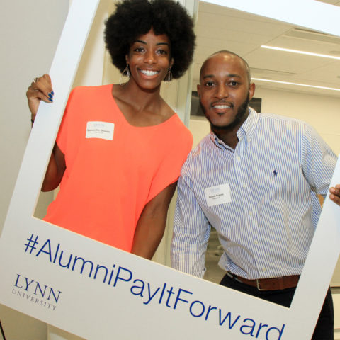 Alumni pose for the camera at pay it forward event.