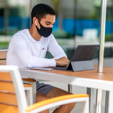 A student sits at a table with his iPad.