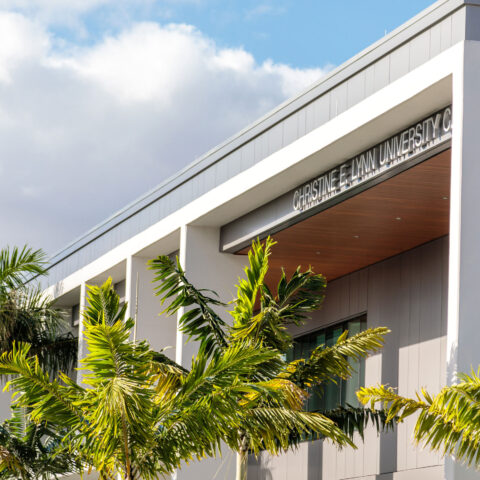Exterior of the Christine E. Lynn University Center with green palm trees in front of it.