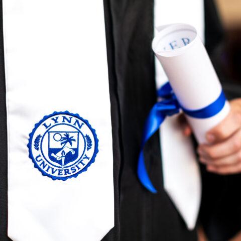 Close up image of graduation regalia and diploma