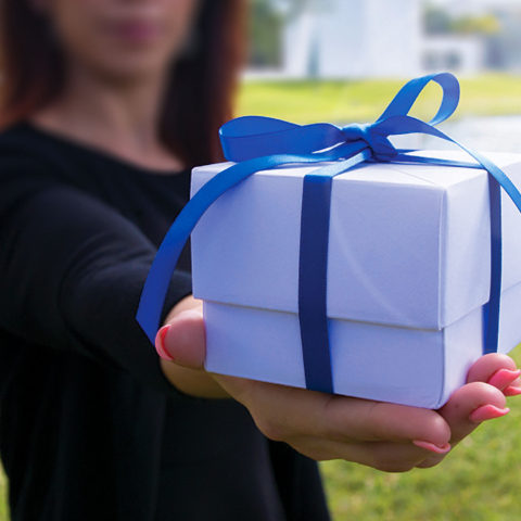 Closeup of woman extending her arm holding a gift