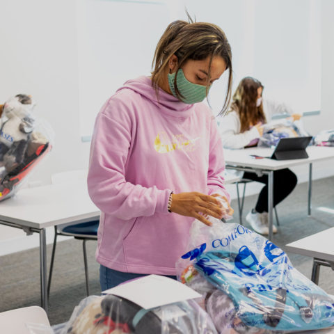 Students packing bags with items donated for the Comfort Cases project in socially distanced classroom.