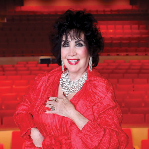 Jan McArt in the theater with red seating backdrop