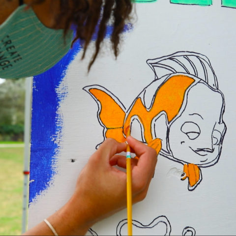 A students paints a mural for a J-Term project.