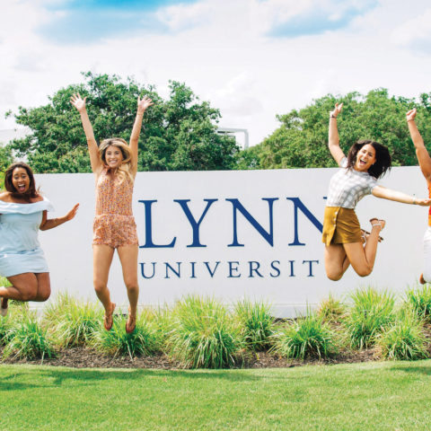 Students jump for joy in front of the campus entrance's Lynn University sign.