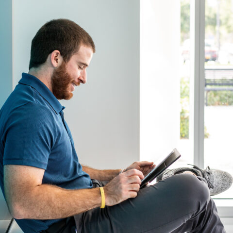 Employee with ipad leaning against blue-colored glass wall