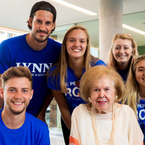 Mary Perper surrounded by students inside the Mary and Harold Perper Residence Hall