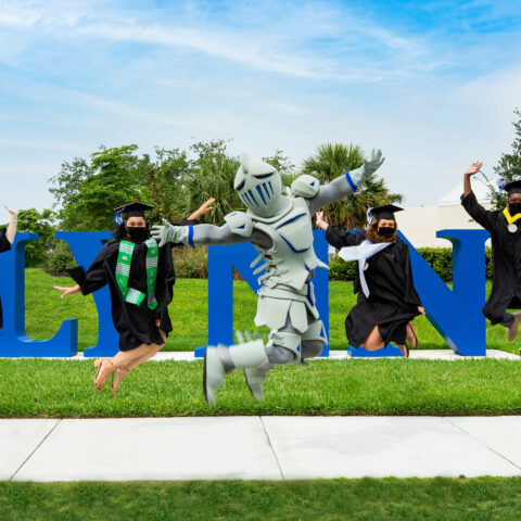 Seniors and Lance the Fighting Knight jump for joy in front of the Lynn letters.