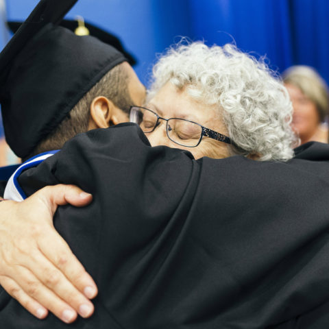 Professor and student hug at undergraduate commencement.