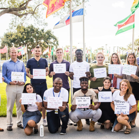 Social entrepreneurship recipients stand in front of the flags.