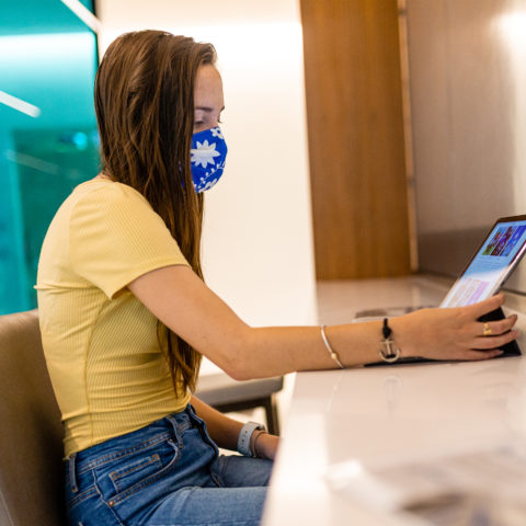 Female student wearing a mask working on iPad.