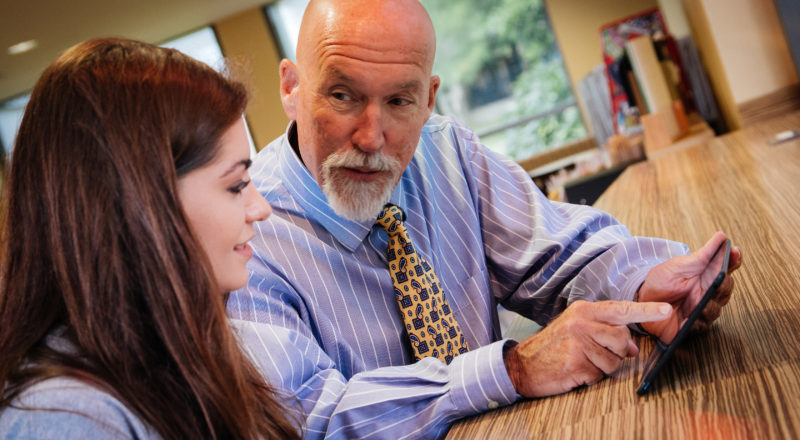 Dr. Gregg Cox meets with student to give tips on Lynn's iPad mini initiatives.