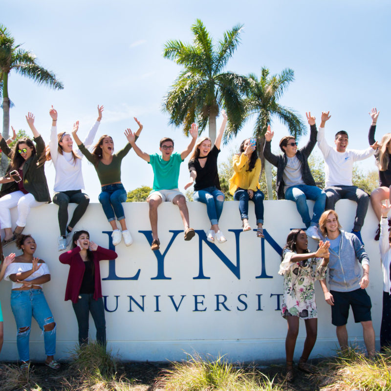 Students sit and cheer on the Lynn University sign.