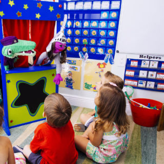Early childhood educator putting on a puppet show for young children.