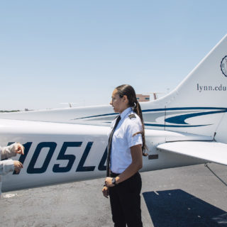Aeronautics students in the private pilot program showing her friend the an aircraft.