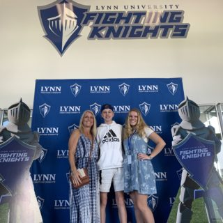 Prospective student with family posing in front of Fighting Knights cutouts.