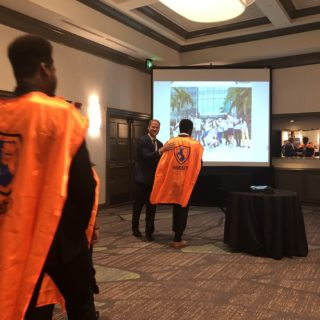 Watson Institute students don orange capes at a Greater Boca Raton Chamber of Commerce breakfast.